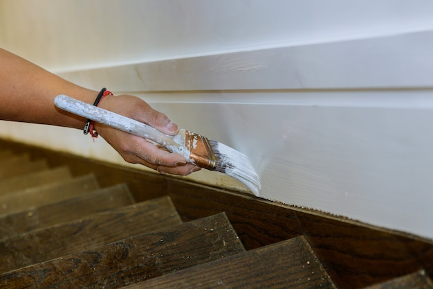 Travailler les mains de peintre entrepreneur avec la peinture de la moulure en bois sur les escaliers avec une brosse