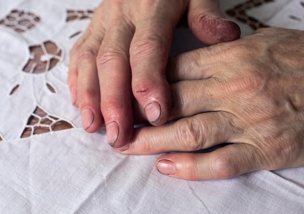 Travailler les mains sales d'une femme âgée après le travail allongé sur une table en gros plan