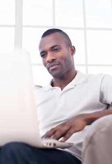 Travailler à la maison. beau jeune homme africain à l'aide d'un ordinateur et assis sur la chaise