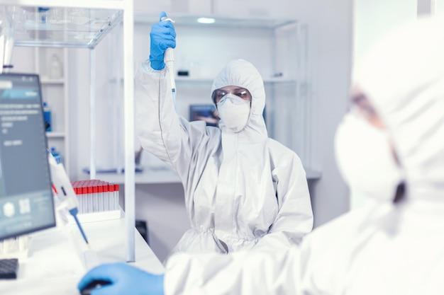 Travailler avec une micropipette en utilisant une combinaison de protection comme précaution de sécurité pour le coroanvirus. équipe de microbiologistes dans un laboratoire de recherche menant une expérience pendant une pandémie mondiale avec covid19.