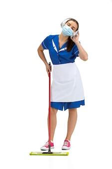 Travailler avec la musique. portrait de femme faite, femme de ménage, ouvrier de nettoyage en uniforme blanc et bleu isolé sur blanc