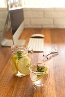 Travailler sur ordinateur à la maison avec de la limonade