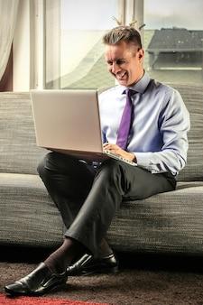 Travailler sur un ordinateur portable sur un canapé