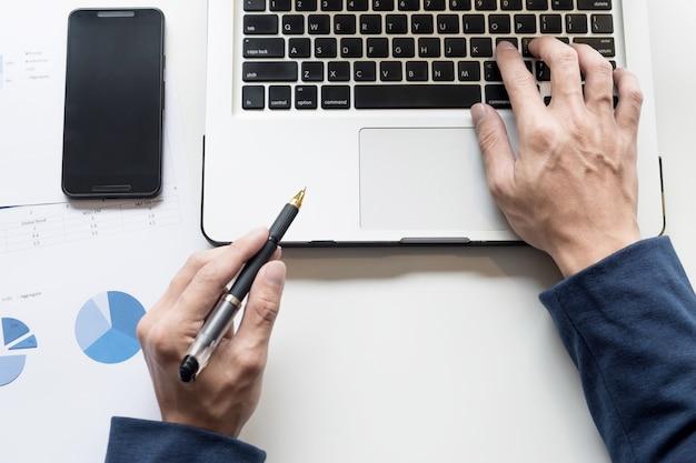 Travailler sur ordinateur portable, gros plan d'homme d'affaires.