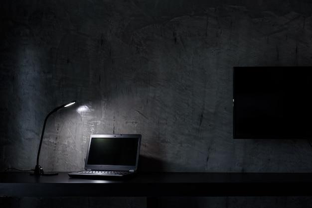 Travailler avec un ordinateur portable noir et une lampe led blanche sur table noire