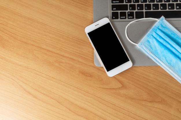 Travailler à partir du concept de la maison. vue de dessus ordinateur portable, smartphone et masque facial sur table en bois.