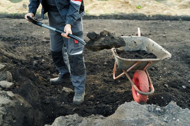 Travailler avec la pelle et la brouette d'outils de jardin sur le site d'une préparation de maison de campagne pour