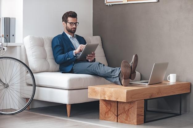 Travailler avec plaisir. beau jeune homme gardant les jambes sur la table et travaillant avec le pavé tactile tout en étant assis sur le canapé au bureau