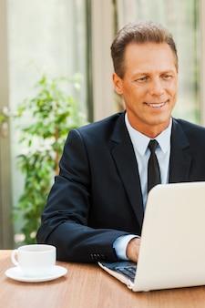 Travailler avec plaisir. homme d'âge mûr gai en tenues de soirée travaillant sur un ordinateur portable et souriant tout en étant assis à la table à l'extérieur