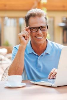 Travailler avec plaisir. homme mûr gai travaillant à l'ordinateur portable et souriant tout en s'asseyant à la table dehors avec la maison à l'arrière-plan