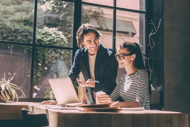 Travailler avec plaisir. jeune homme et femme confiants regardant un ordinateur portable et souriant tout en étant assis au bureau en bois dans un bureau ou un café créatif