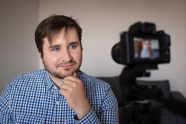 Travailler pour vous. beau contenu jeune homme souriant et réalisant une vidéo à la maison