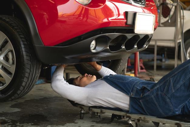 Travailler sous la voiture au garage de service automobile