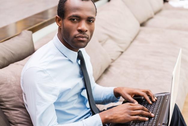 Travailler en toute confiance. vue de dessus du jeune homme africain en tenue de soirée travaillant sur ordinateur portable