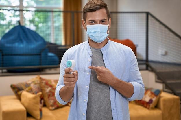 Travailler en toute sécurité portrait d'un jeune homme portant un masque de protection médical debout dans le bureau et