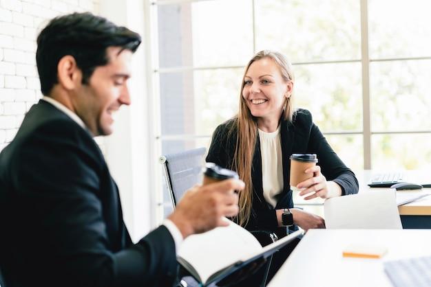 Travailleur d'affaires caucasien homme et femme parlant à travers la table avec un sourire et se détendre.