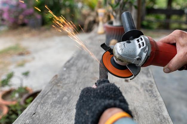 Le travailleur affûte la pelle à lame avec la scie électrique et l'étincelle