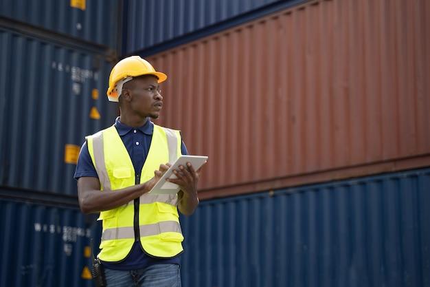 Travailleur africain tenant une tablette, marchant et vérifiant la boîte des conteneurs du cargo pour l'exportation et l'importation