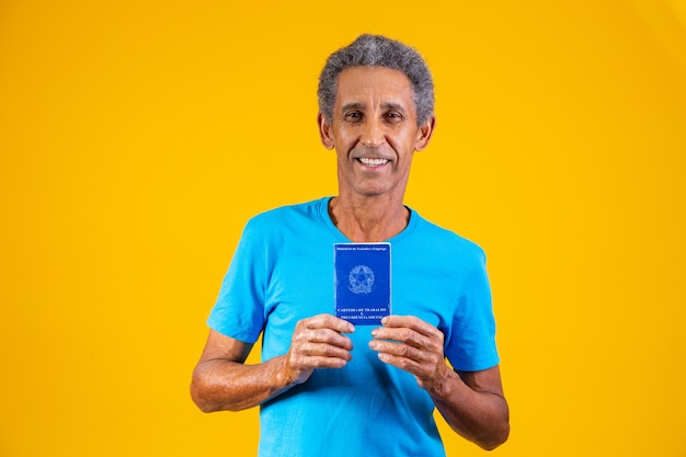 Travailleur âgé tenant une carte de travail brésilienne à la main. personne âgée tenant une carte de travail brésilienne