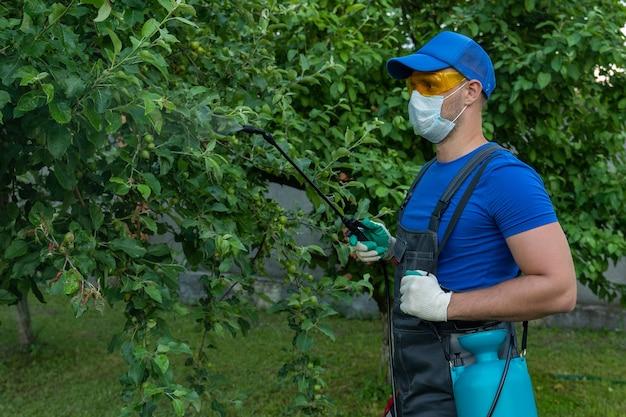 Travailleur d'agriculteur d'homme pulvérisant le traitement de pesticide sur le jardin de fruit