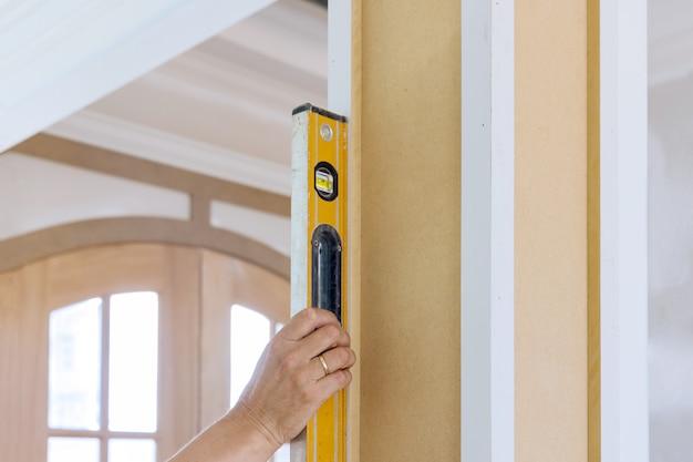 Le travailleur à l'aide d'un instrument de nivellement vérifie les colonnes de bois appropriées à l'aide du niveau en construction