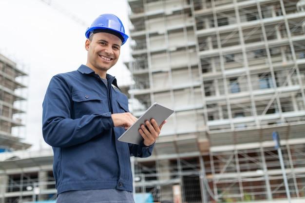 Travailleur à l'aide de sa tablette devant un chantier de construction