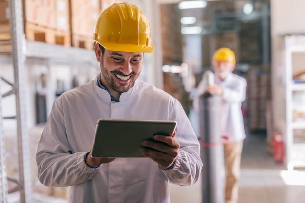 Travailleur à l'aide de tablette en entrepôt.