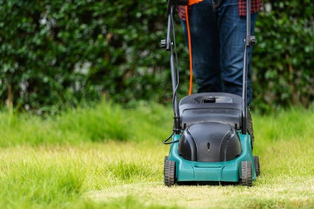 Travailleur à l'aide d'une tondeuse à gazon coupant l'herbe à la maison