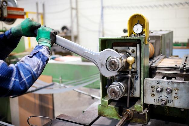 Travailleur ajustant les machines avec une grande clé