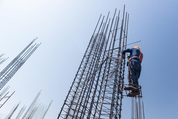 Le travailleur en altitude renforce les piliers des barres d'armature sur le fond de ciel bleu