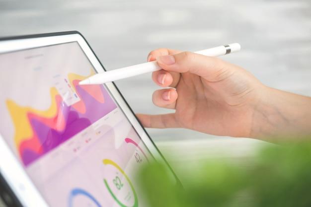 Travailleur analysant les résultats financiers sur tablette numérique à l'aide d'un stylet sans fil. diagramme d'affaires sur l'écran, photo d'arrière-plan de bureau