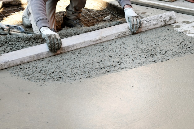 Travailleur aplatir le sol en béton