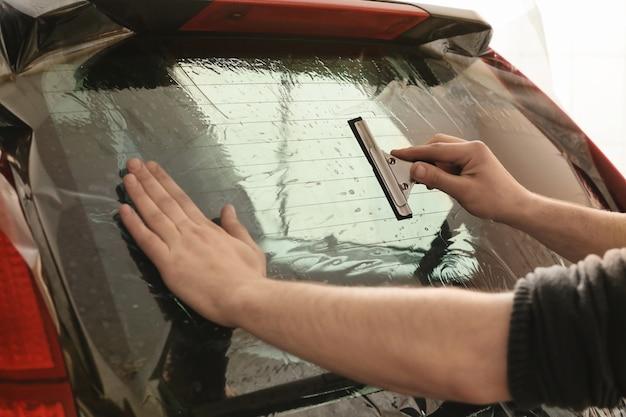 Travailleur appliquant une feuille de teinture sur la fenêtre de la voiture