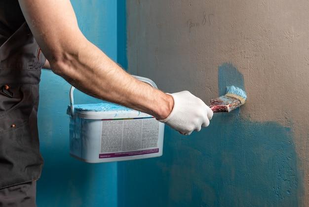 Le travailleur appliquant une peinture d'étanchéité sur le mur de la salle de bain
