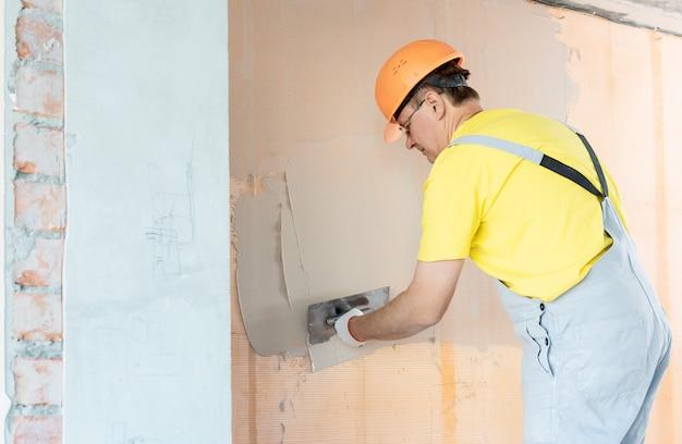 Le travailleur applique du mastic sur une maille en fibre de verre sur le mur.