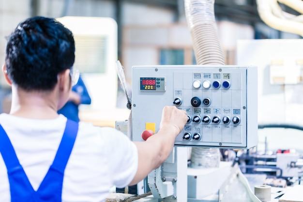 Travailleur en appuyant sur les boutons sur la carte de commande de la machine cnc dans l'usine asiatique