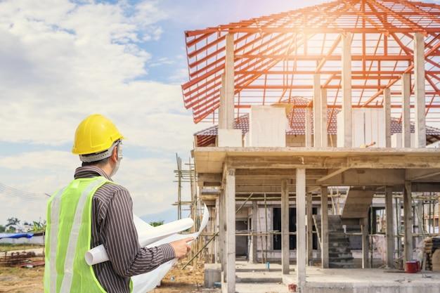 Travailleur d'architecte ingénieur professionnel avec casque de protection et papier de plans au fond de chantier de construction de bâtiments