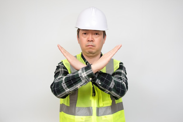 Un travailleur asiatique d'âge moyen qui lève la main et exprime sa désapprobation.