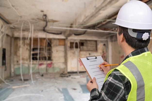 Un travailleur asiatique d'âge moyen vérifiant quelque chose avec une liste de contrôle à la main.