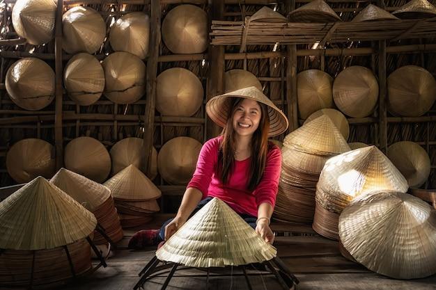 Travailleur asiatique femme artisan faisant le traditionnel chapeau vietnamien dans l'ancienne tradition