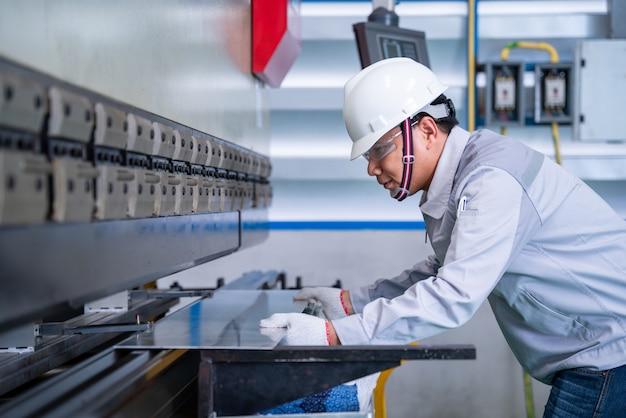 Travailleur asiatique portant un costume de sécurité et réglage de la machine hydraulique