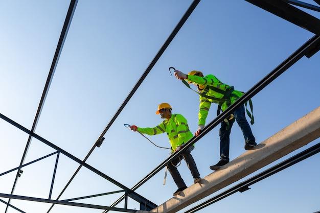 Un travailleur asiatique porte un équipement de hauteur de sécurité pour construire une structure de toit en acier sur le chantier de construction.