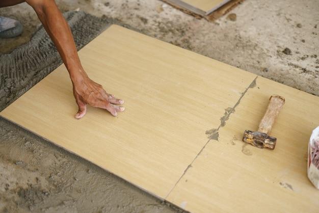 Travailleur asiatique pose carreaux de sol