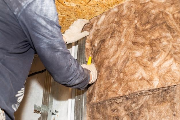 Le travailleur attache de la laine minérale aux murs pour une isolation thermique supplémentaire du revêtement en plaques de plâtre