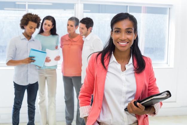 Travailleur attrayant avec planificateur sourit à la caméra avec des collègues en arrière-plan