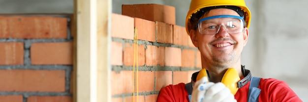 Travailleur au chantier de construction faisant un geste d'amitié dans des gants de protection headshot