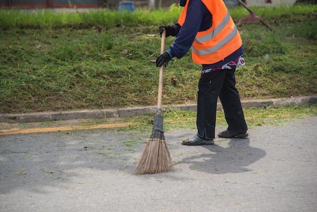 Travailleur de balayeuse de route nettoyage rue de la ville avec un outil de balai en thaïlande