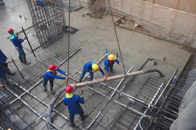 Le travailleur en bleu travaillant dans un chantier de construction avec du ciment
