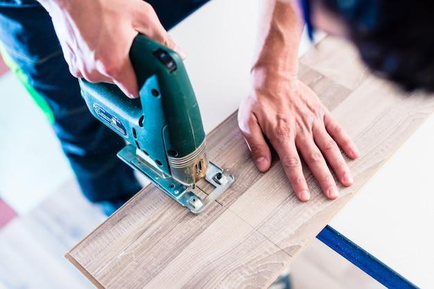 Travailleur de bricolage coupe un panneau en bois avec une scie sauteuse