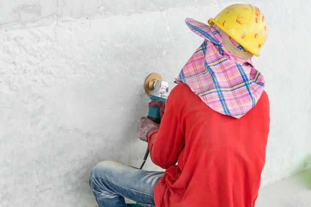 Travailleur broie le mur de béton avec une rectifieuse angulaire sur un chantier de construction.